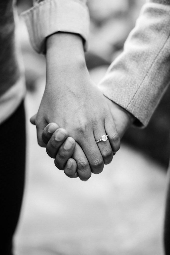 Close up couple holding hands with engagement ring