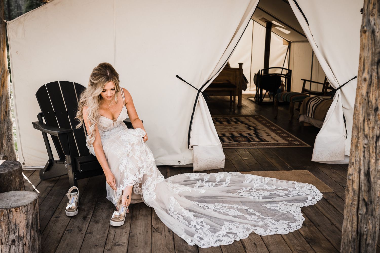 Bride puts on her shoes in front of glamping tent at Piney River Ranch Vail CO