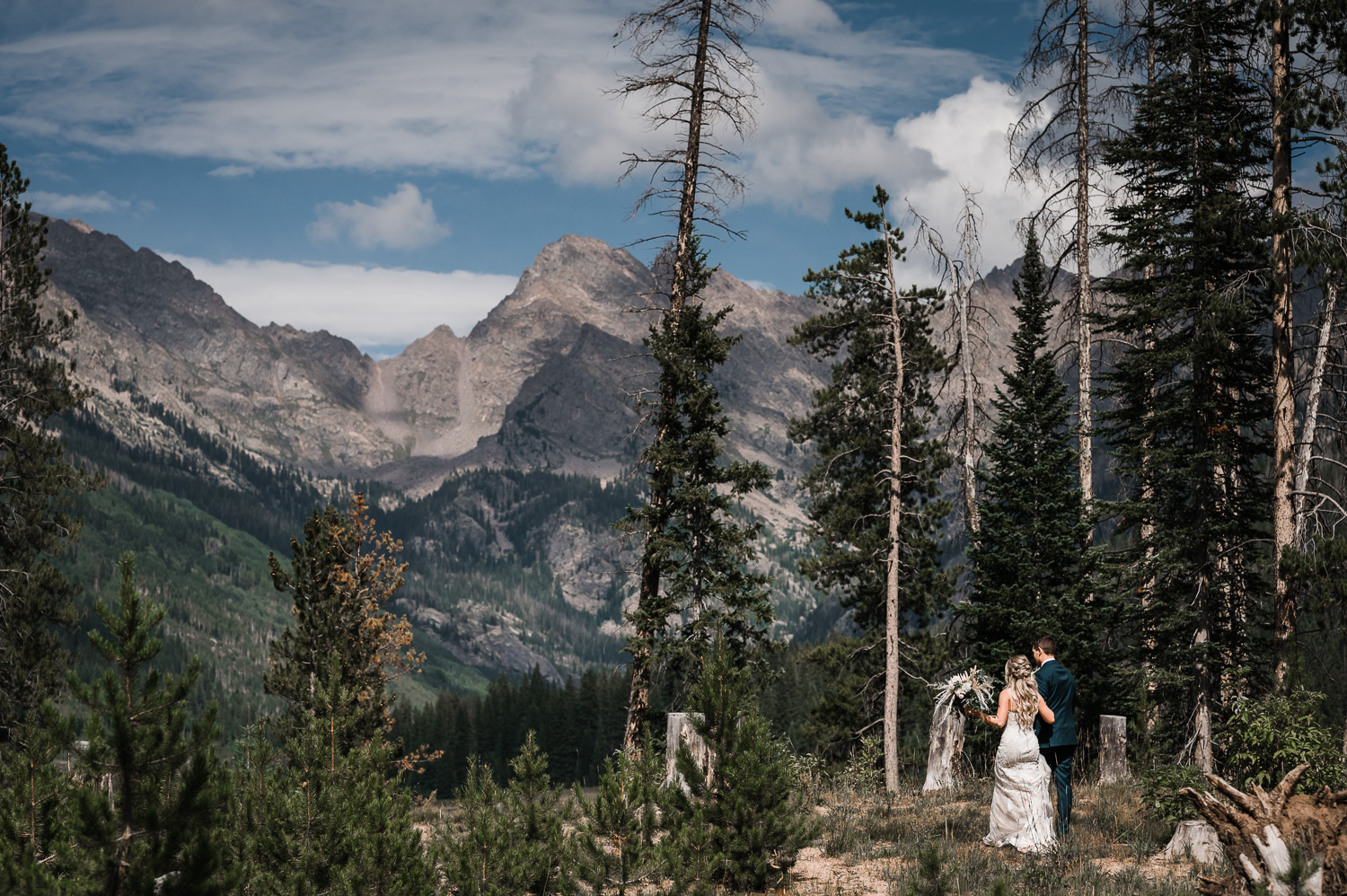 Bride and Groom walk together through the rocky mountains with epic view