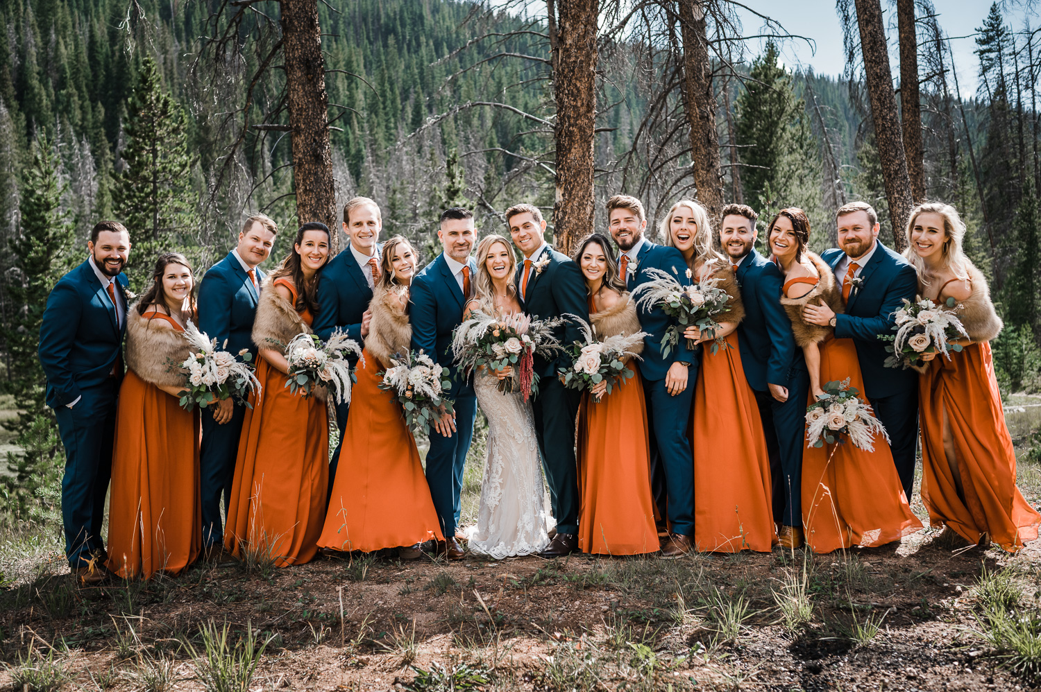 Bridal party squeezes into bride and groom, wearing rust and blue colors