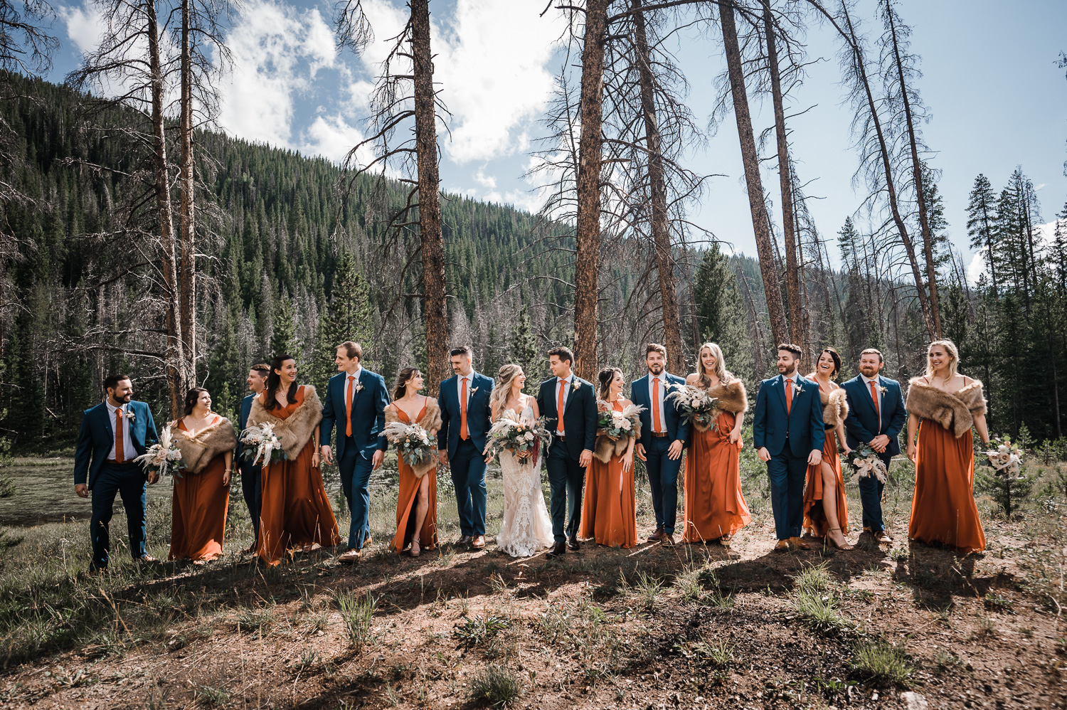 Fun bridal party at mountain wedding in CO, wearing rust and blue colors