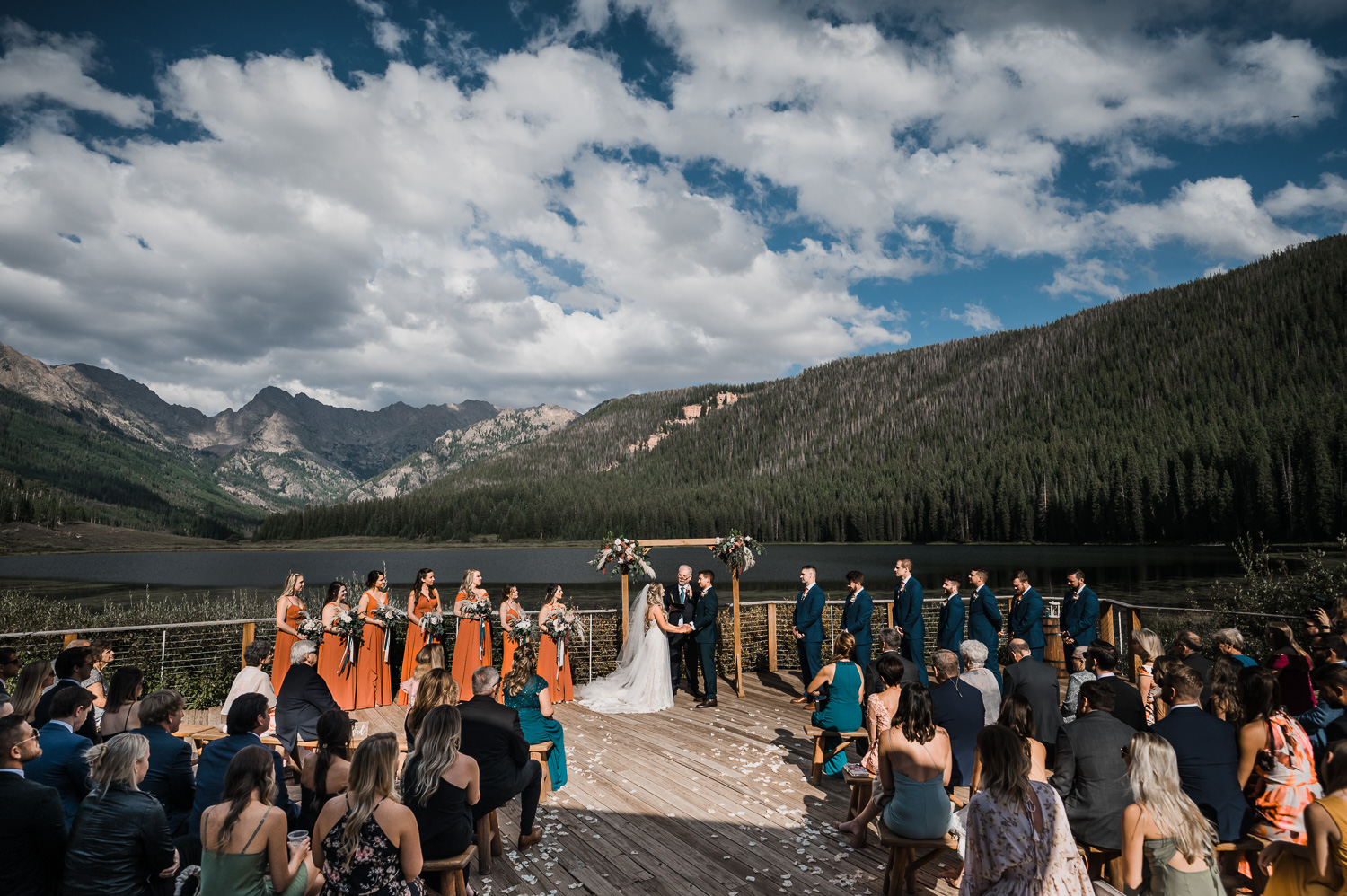 Piney River Ranch Lake Dock Wedding Ceremony in front of mountains with rust color bridesmaids dresses and blue suits for groomsmen