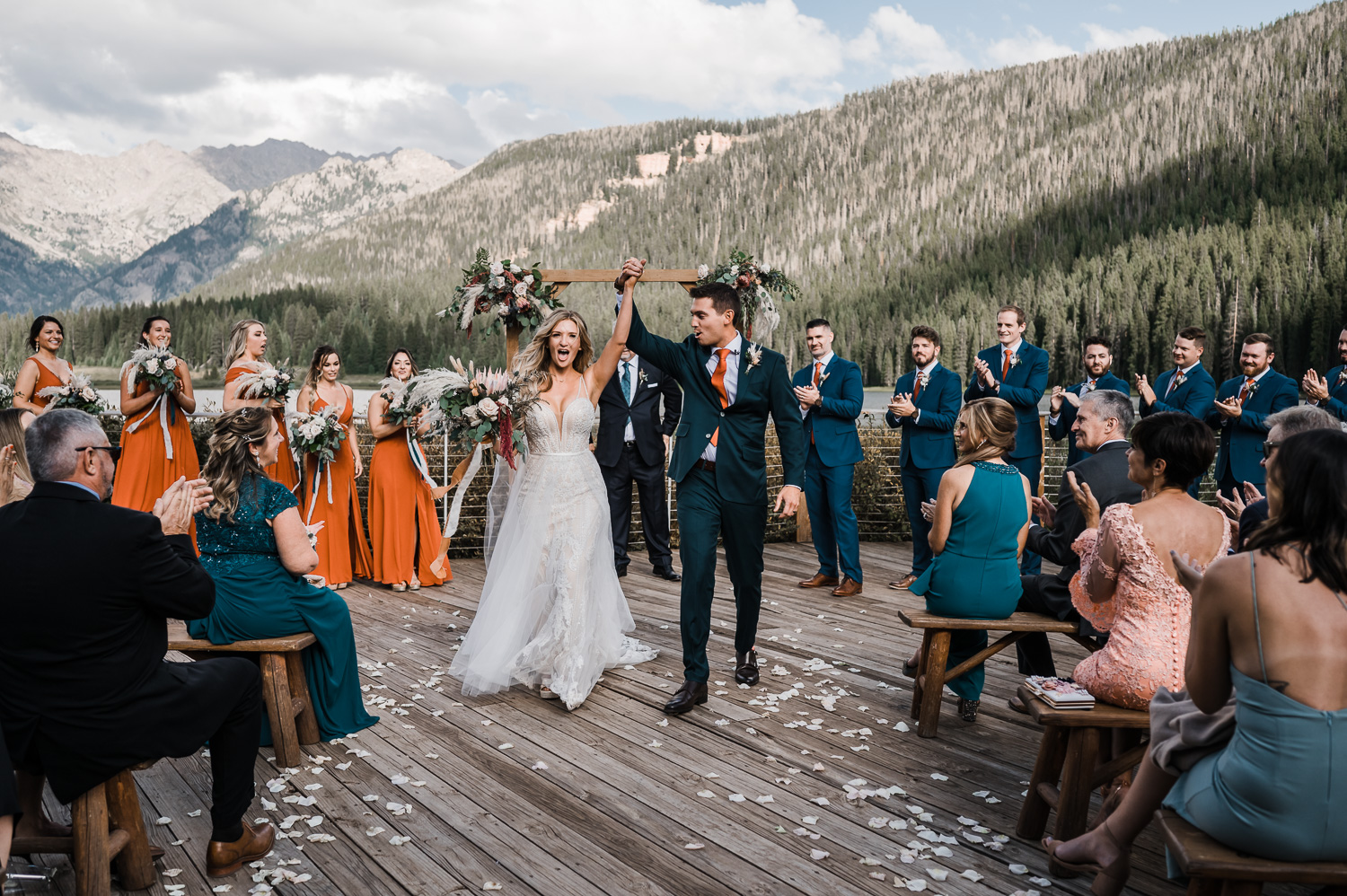 Bride and Groom hold hands and cheer while walking down aisle after wedding at Piney River Ranch