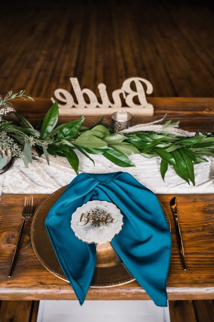 Wedding table setting with rust and teal colors and rock slice name card