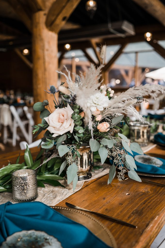 Wedding farm table setting with gold and teal colors