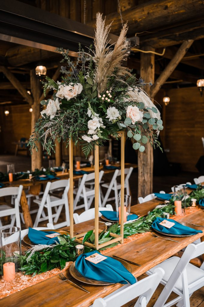 Wedding farm table setting with rust and teal colors and column florals