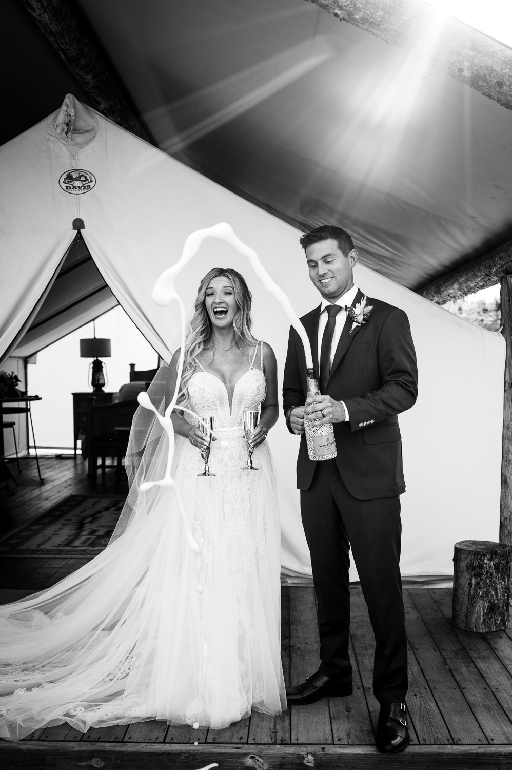 Bride and Groom laugh as Champagne sprays out over their heads in front of glamping tent at Piney River Ranch Colorado