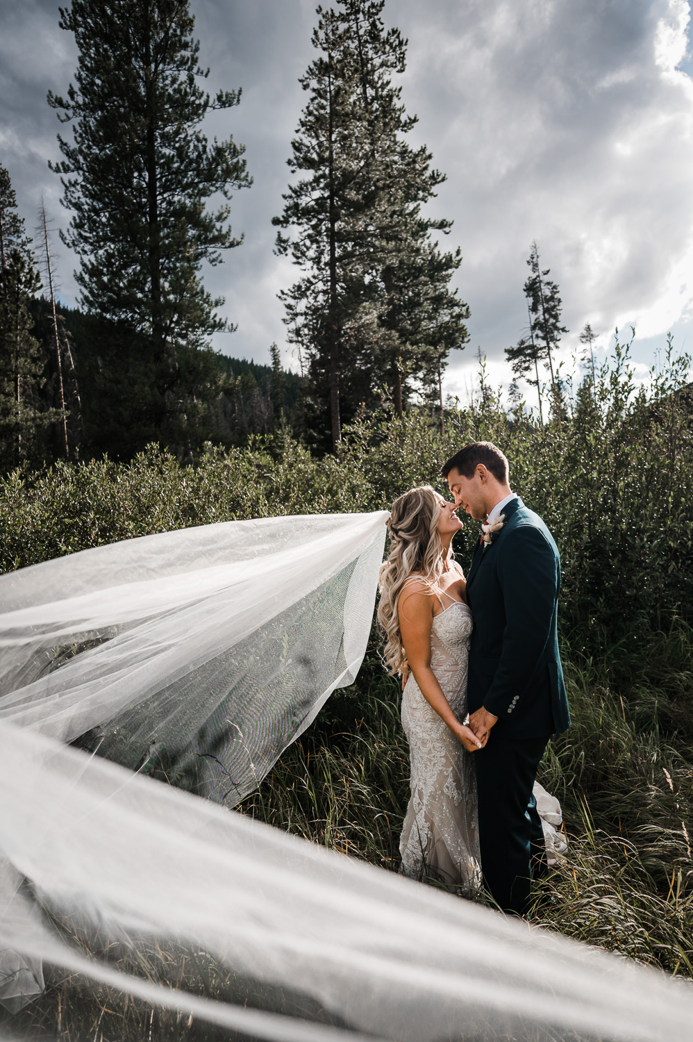 Bride and groom kiss while veil flows in wind at Piney River Ranch Vail CO