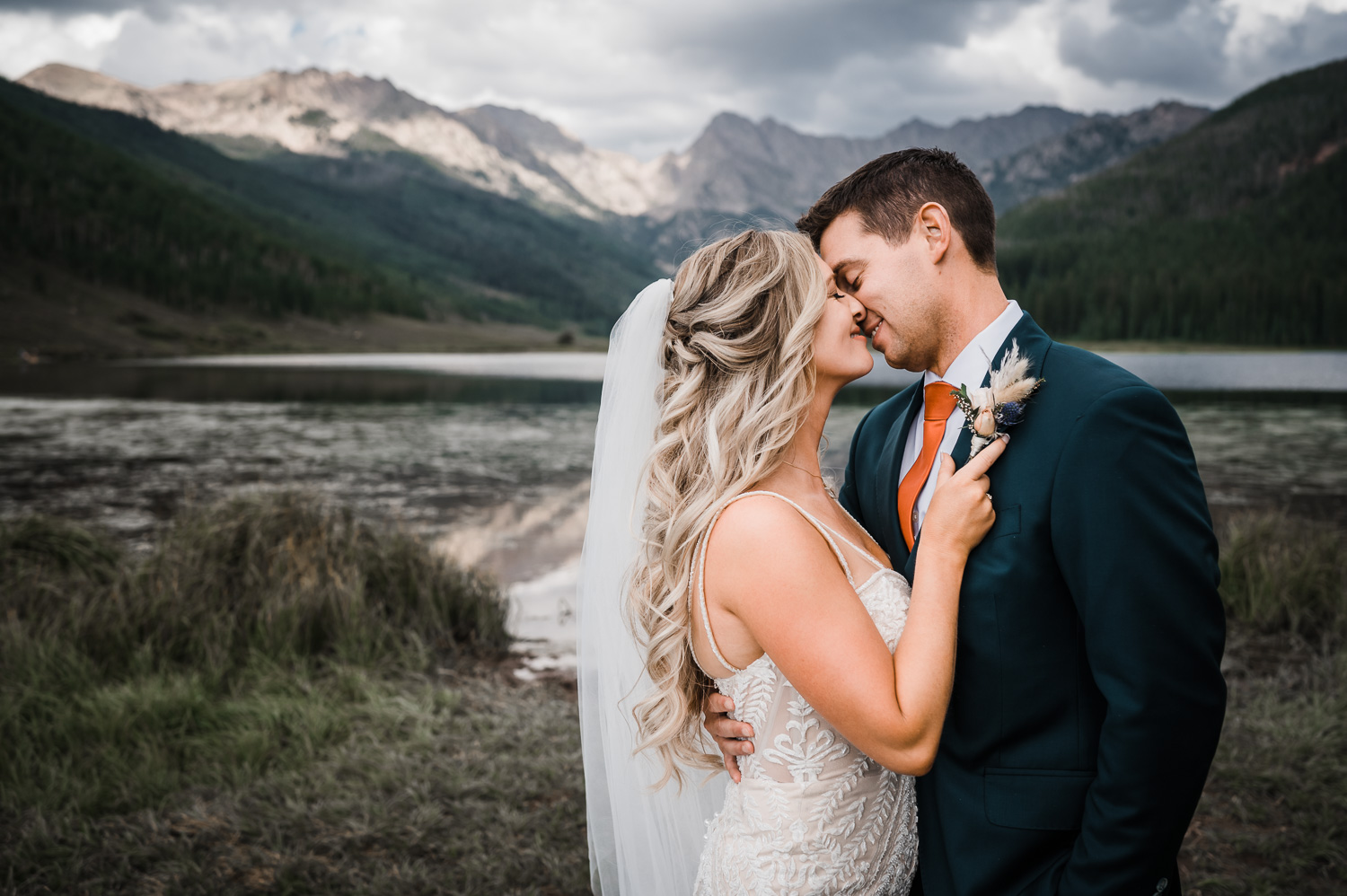 Bride pulls Groom in for kiss in front of Piney Lake with Mountains behind them
