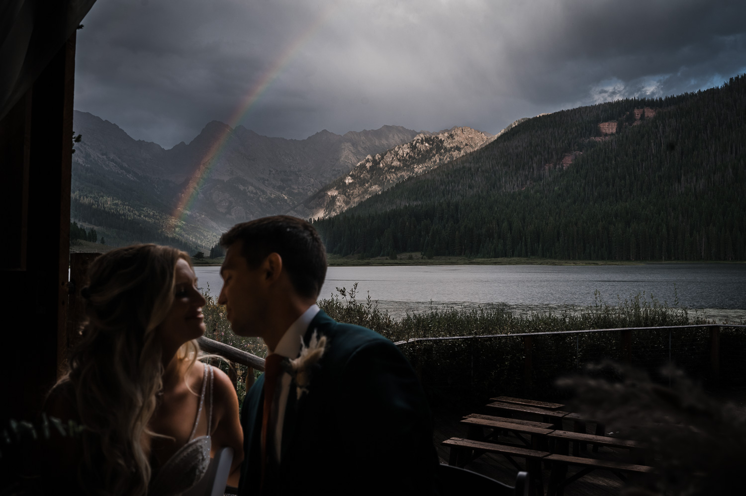 Bride and groom kiss as a Rainbow appears on the mountain behind them at Piney River Ranch