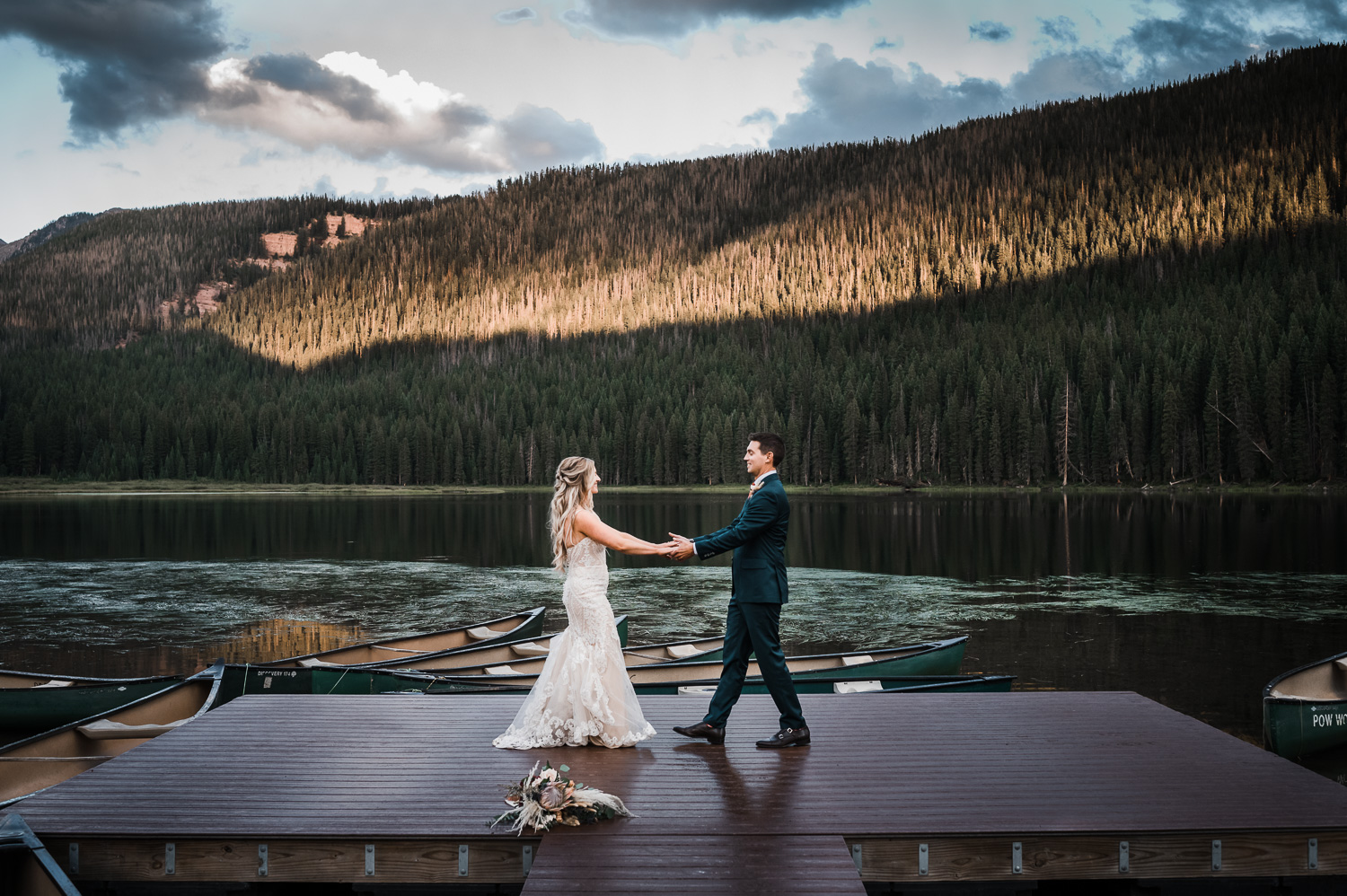 Bride and Groom dance on the lake dock at Piney River Ranch