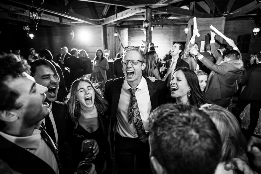 Guests at a wedding in a circle belt out a songs on the dancefloor