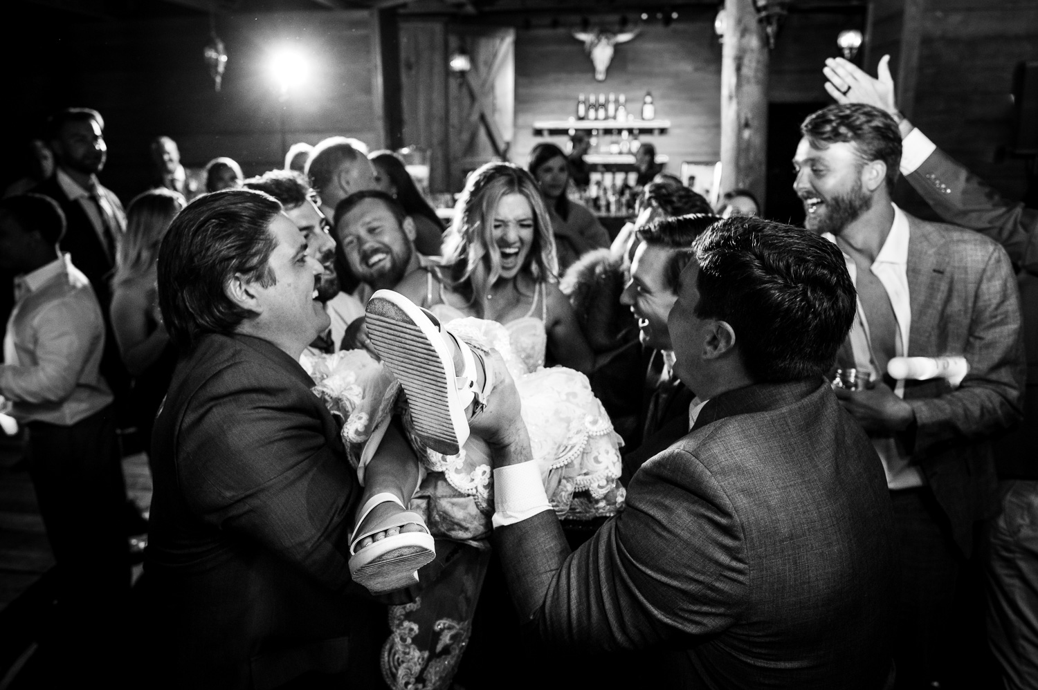 Bride laughs and screams are she is tossed in the air by groomsmen